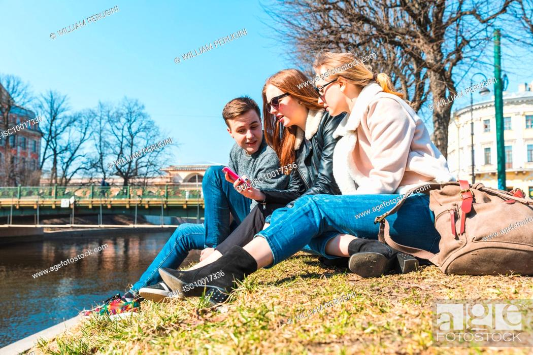 Imagen: Friends using smartphone in city, Saint Petersburg, Russia.