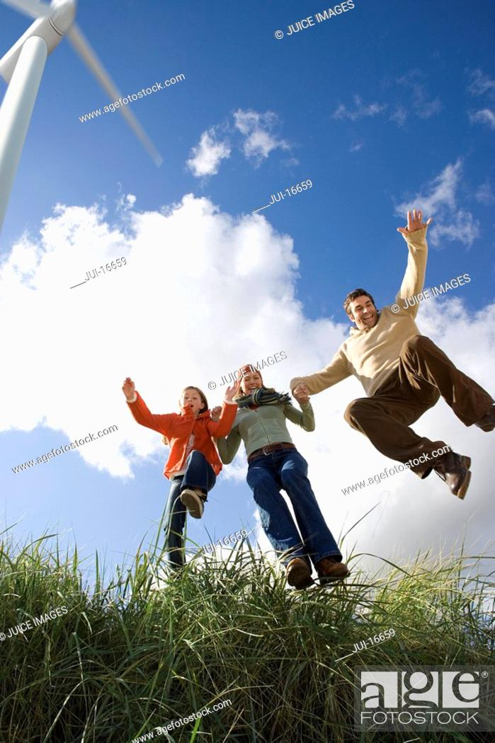Stock Photo: Family jumping in grass.