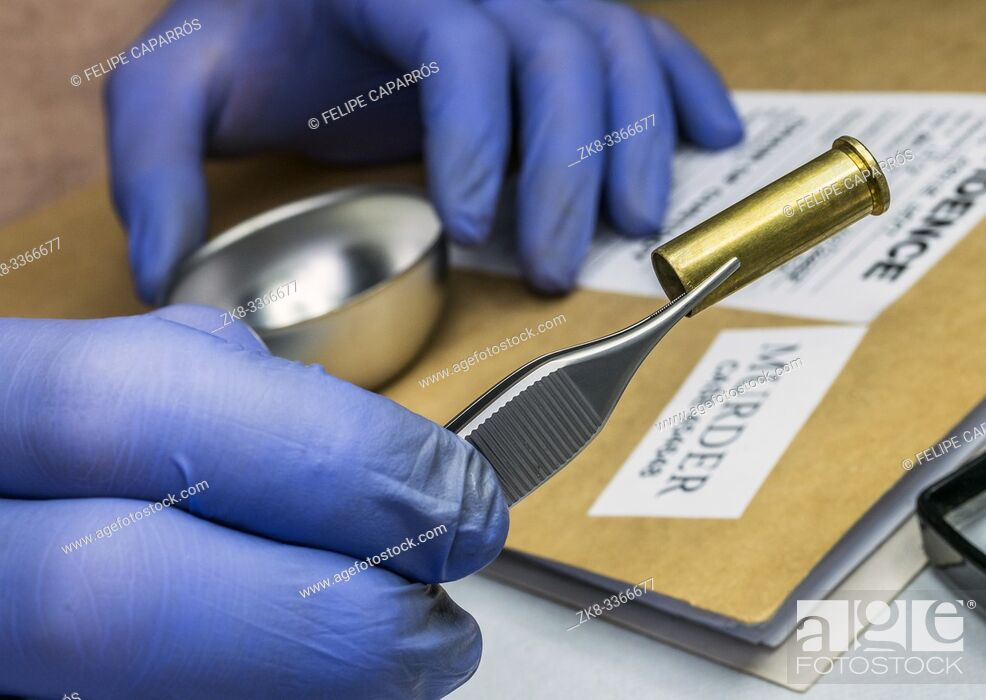 Stock Photo: Scientific police examining a bullet cap in ballistic Laboratory, conceptual image.