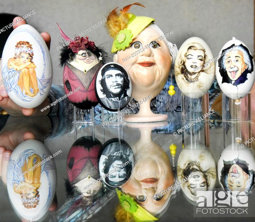 Stock Photo: 28 February 2020, Saxony, Leipzig: On a glass table of the collector and Easter egg artist Kerstin Dischereit there are (r-l) two goose eggs with the portraits.