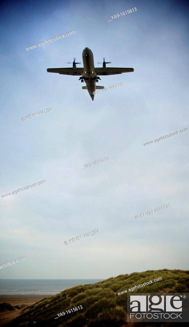 Stock Photo: Aircraft coming into land over the sea and sand dunes.