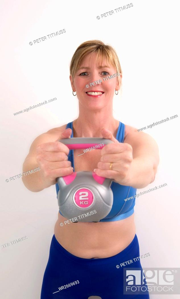 Stock Photo: Woman using a 2 kg weight kettle bell to exercise.