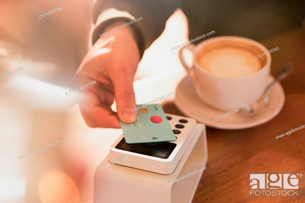 Stock Photo: Close up man paying for cappuccino with credit card contactless payment in cafe.