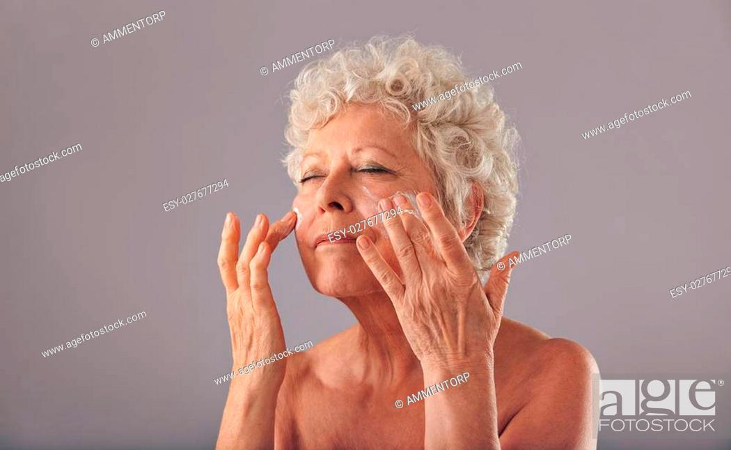 Stock Photo: Portrait of beautiful old woman applying moisturizer on her face against grey background. Senior woman using cosmetics on her face.