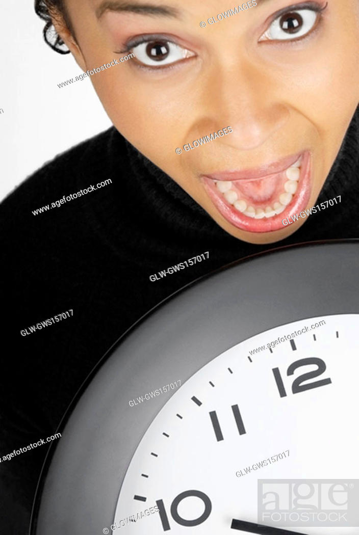 Stock Photo: Portrait of a businesswoman holding a clock with her mouth open.