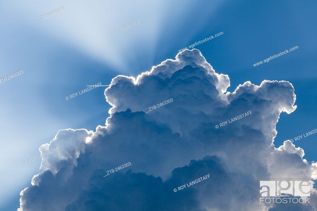 Stock Photo: Rapidly building cloud screening the sun with an aircraft in the sky.
