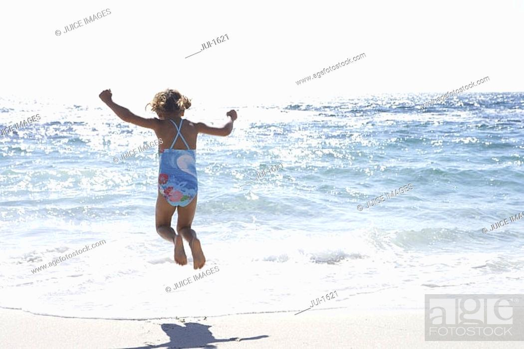 Stock Photo: Girl 3-5 wearing swimsuit, jumping above surf on sandy beach, rear view, sea shimmering in sunlight.