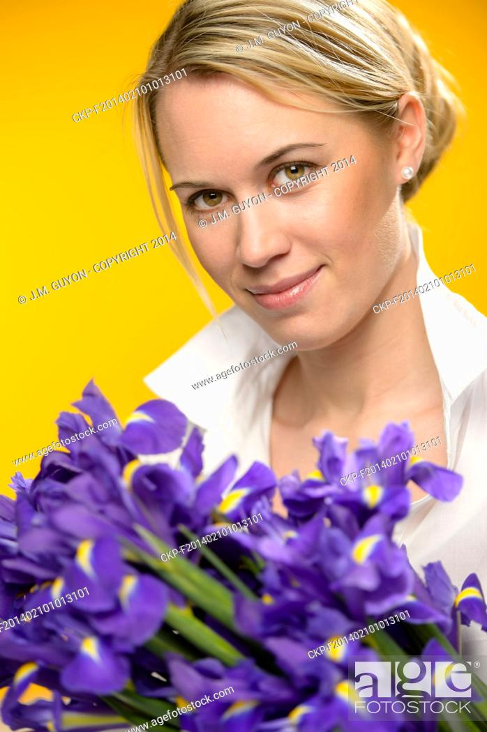Imagen: Woman with spring flowers purple iris on yellow background.