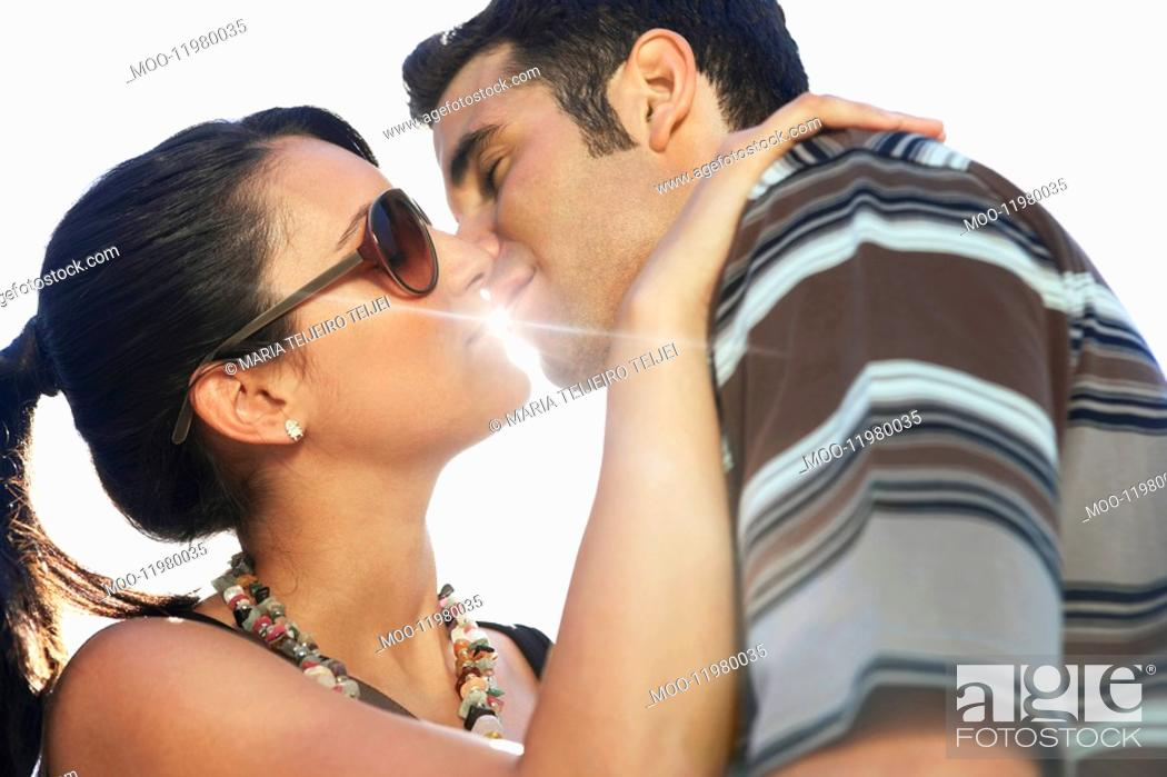 Stock Photo: Young couple kissing portrait side view.