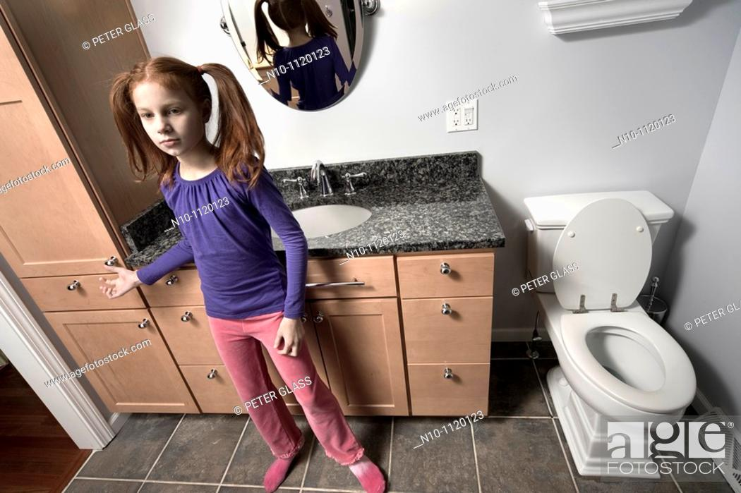 Stock Photo: Preteen redhead girl in her bathroom.