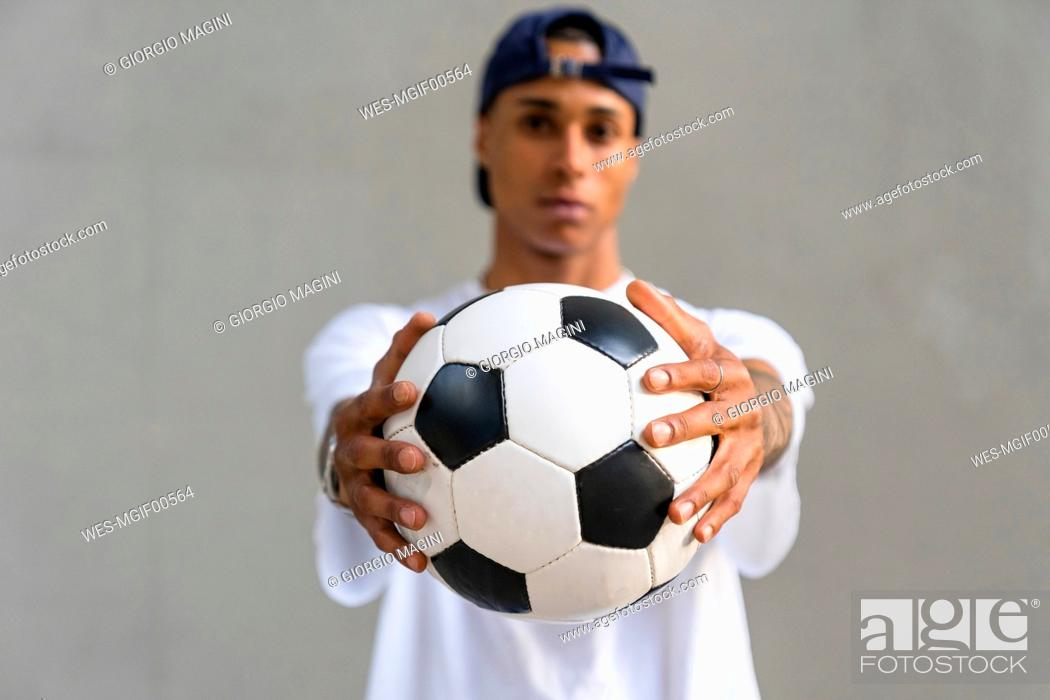 Stock Photo: Young man's hands holding football, close-up.