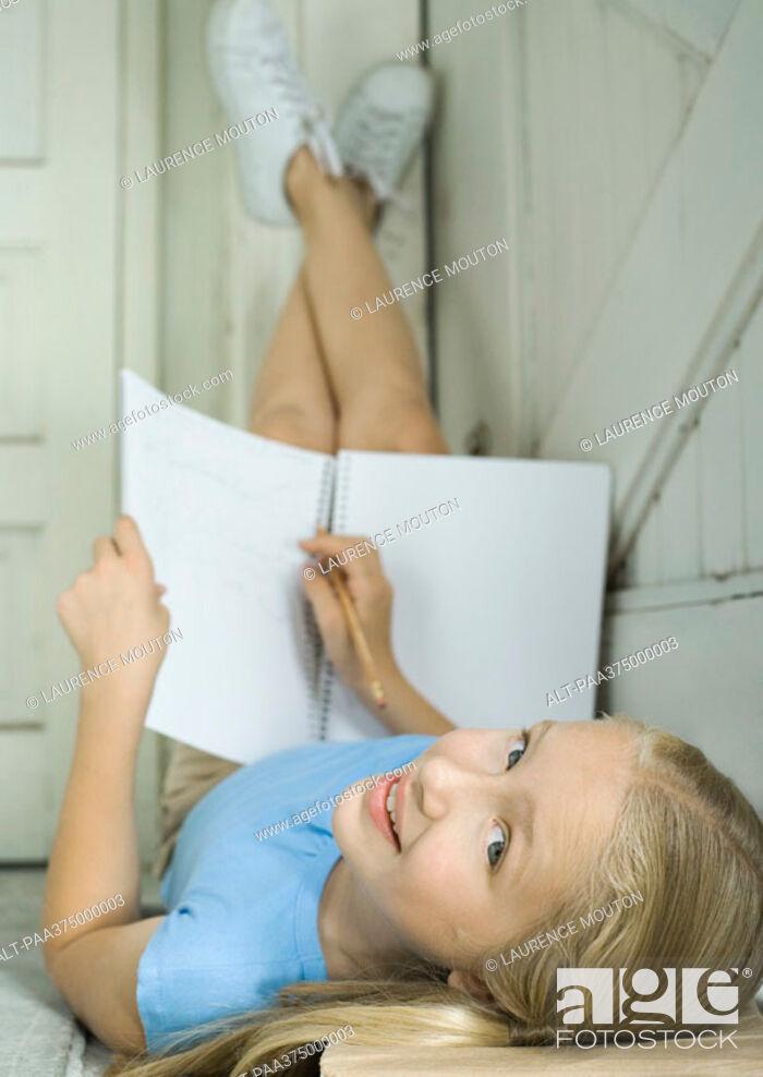 Stock Photo: Girl doing homework with legs up.