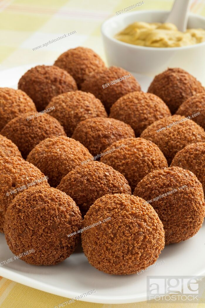 Photo de stock: Dutch traditional snack bitterballen on a dish with mustard in the background.