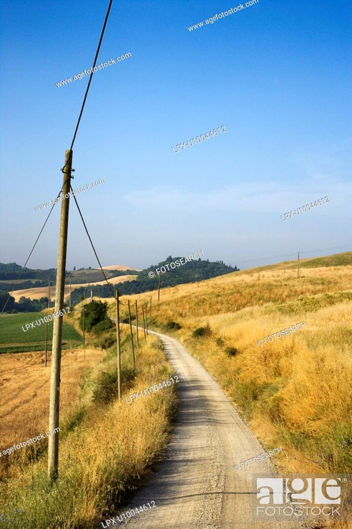 Stock Photo: Telephone poles beside dirt road leading through rolling hills in countryside of Tuscany, Italy.
