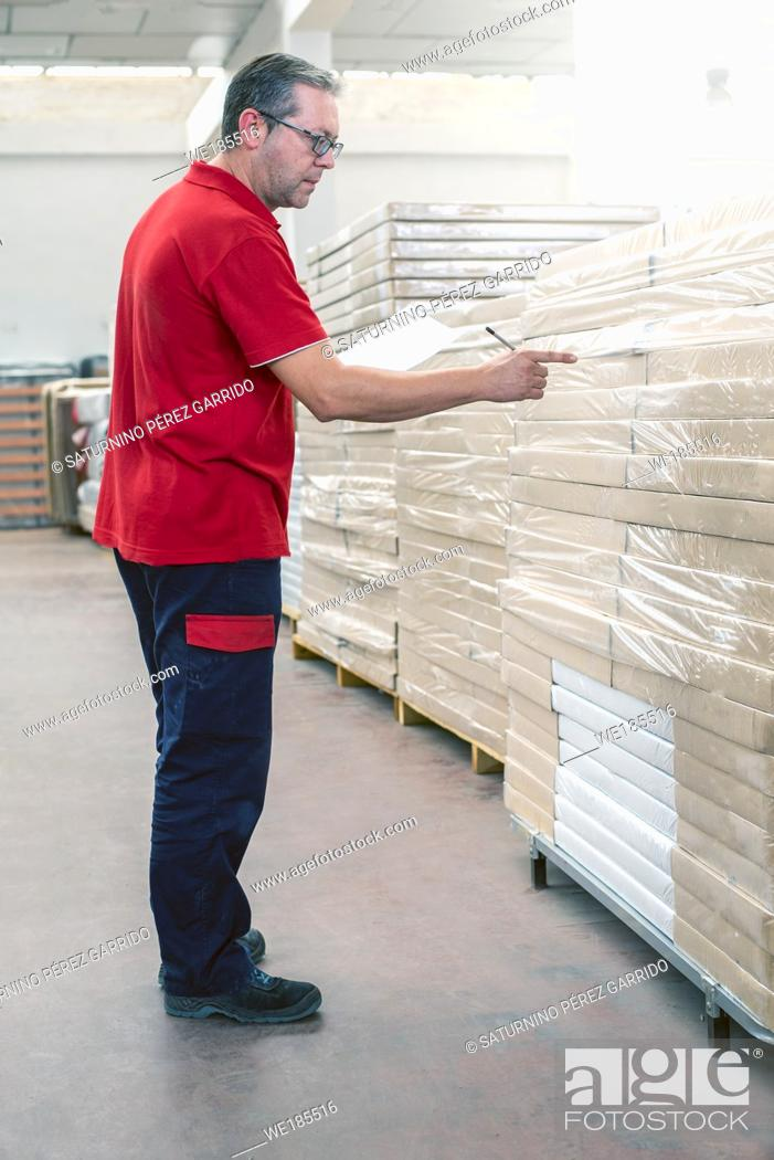 Stock Photo: Warehouse employee checking the stock of stored products.