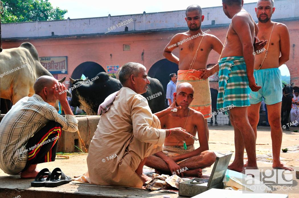 Stock Photo: Pilgrims shaving hair at the ghat by the Ganges river.
