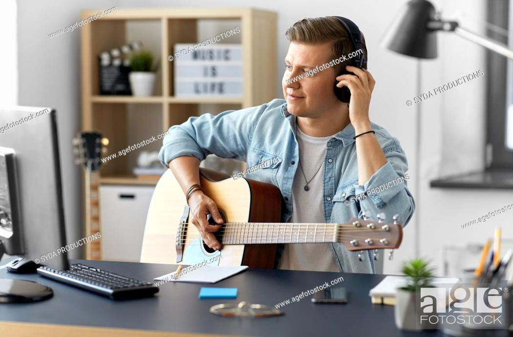 Imagen: man in headphones playing guitar at home.