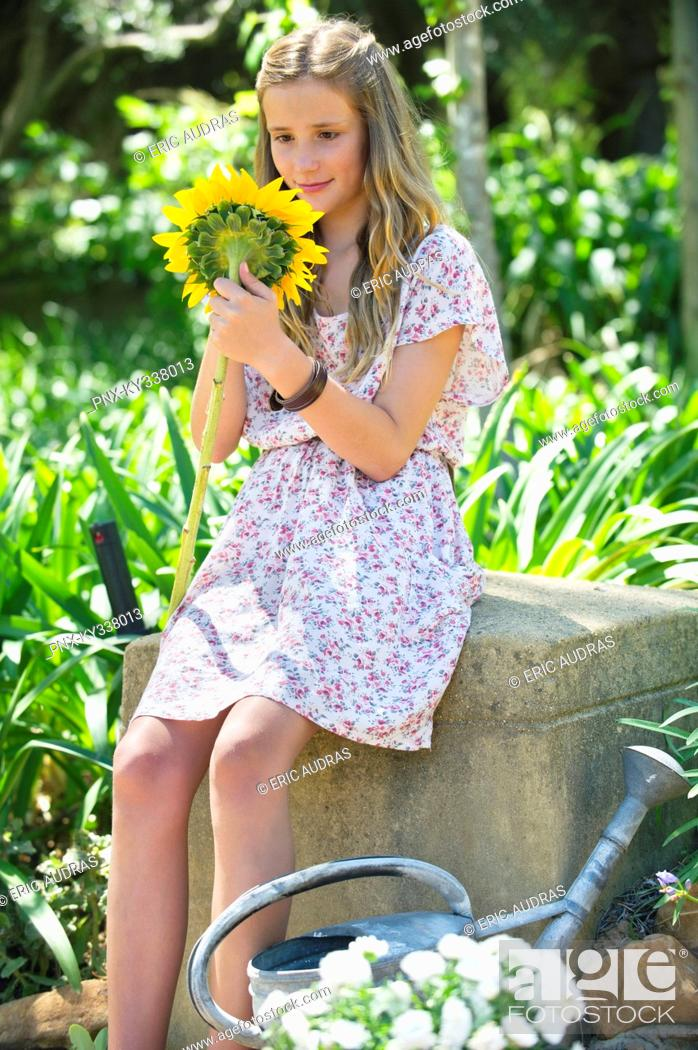Stock Photo: Cute little girl holding sunflower outdoors.
