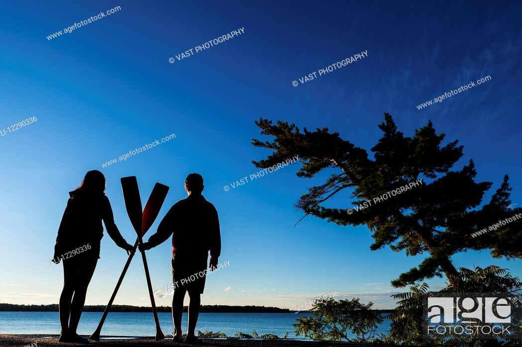 Photo de stock: Boy and girl holding paddles overlooking Balsam Lake at sunrise; Ontario, Canada.