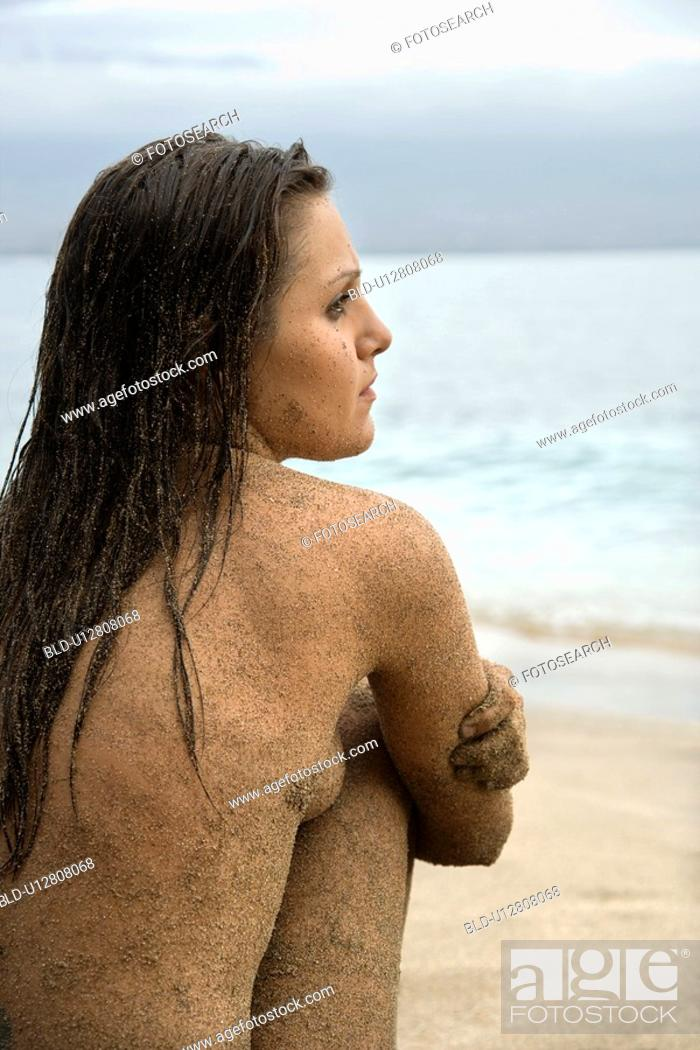 Stock Photo: Side view of young adult nude woman sitting on beach.