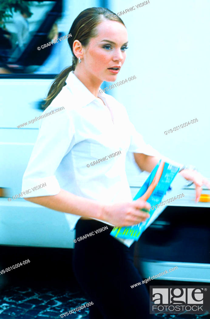 Stock Photo: Young woman walking with a magazine in her hand.
