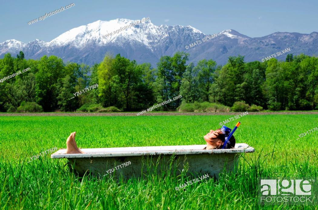 Stock Photo: Woman lying in a bathtub on a green field with grass and trees and with snow-capped mountains.