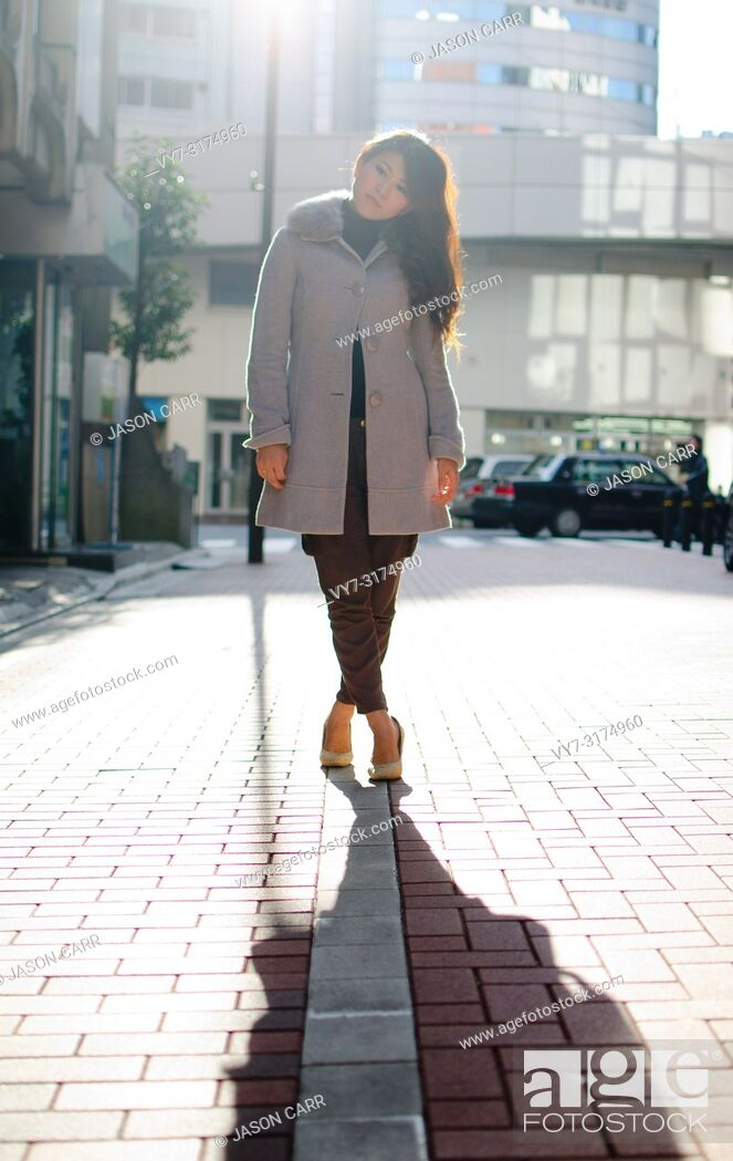 Stock Photo: Japanese Girl poses on the street in Ginza, Japan. Ginza is a shopping city located in Tokyo.