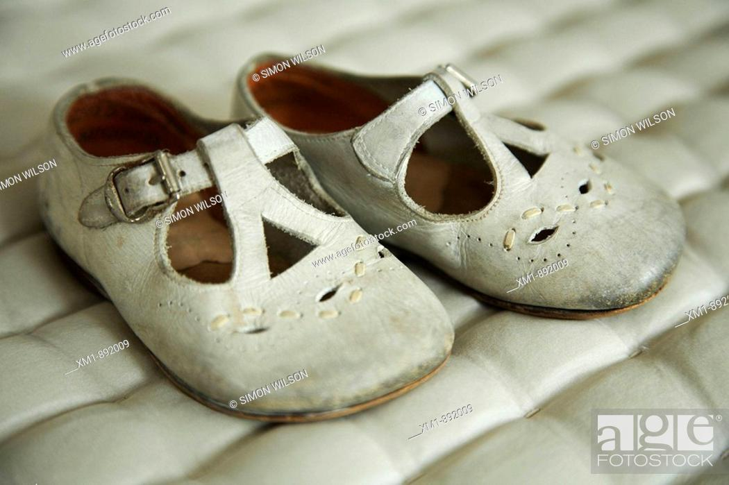 Stock Photo: Old baby's shoes on quilted material.