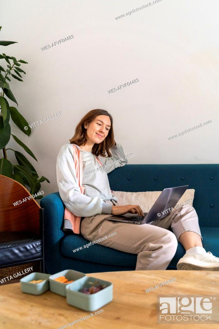 Stock Photo: Young woman sitting on couch using laptop.