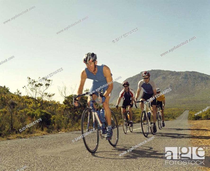 Stock Photo: Four bikers racing down the road.