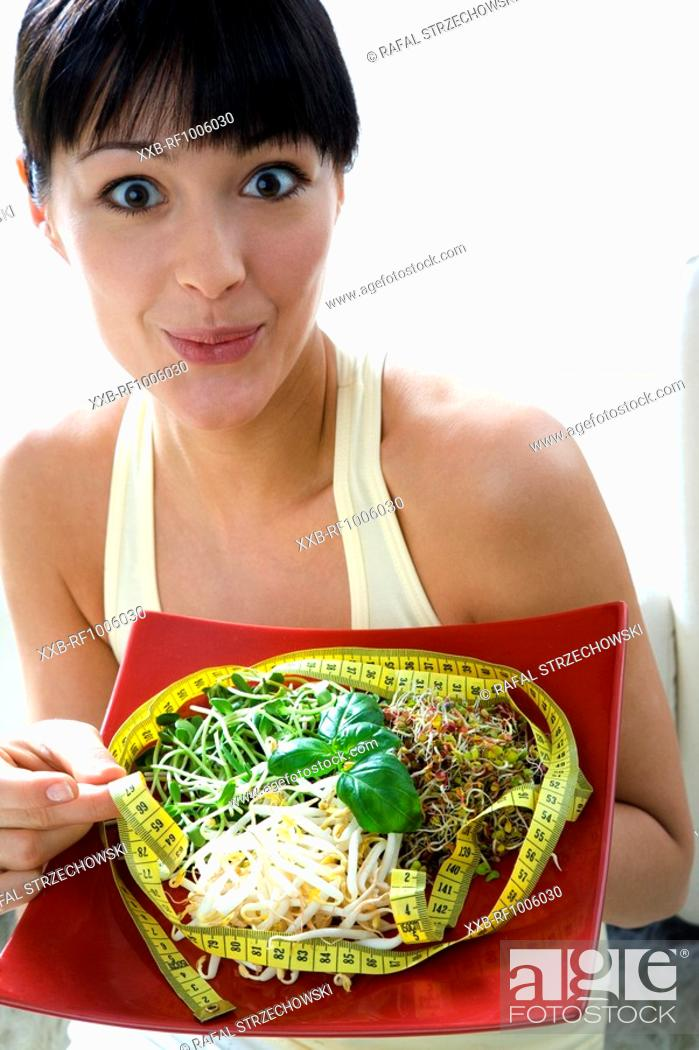Stock Photo: young woman with sprouts and measuring tape.