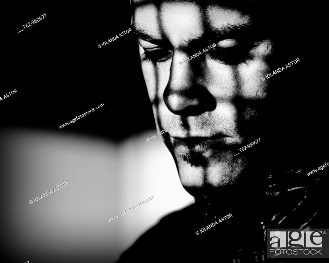 Photo de stock: Young man behind bars  Black and white  Conceptual.