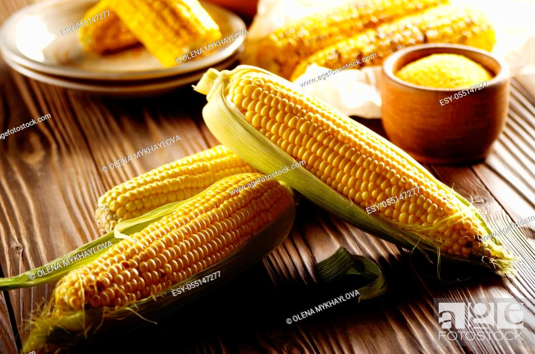 Stock Photo: Kitchen table with raw and grilled sweet corn cob on baking paper and grits in wooden bowl.