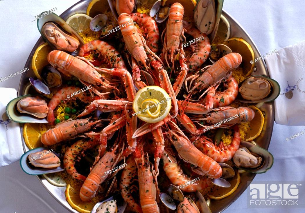 Stock Photo: paella rice with prawns and shellfish on white background.