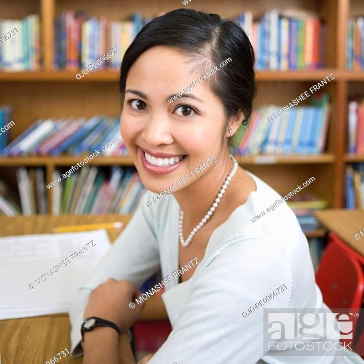 Stock Photo: Teacher sitting in library.