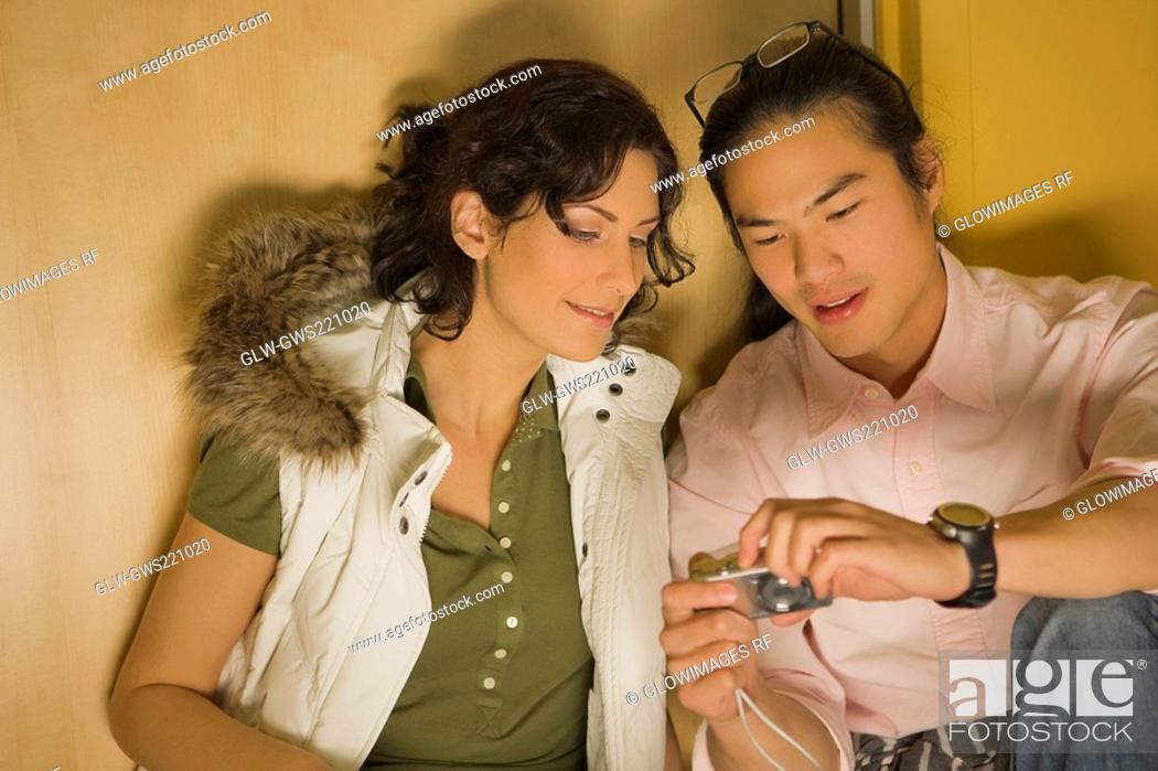 Stock Photo: Young couple looking at a digital camera.