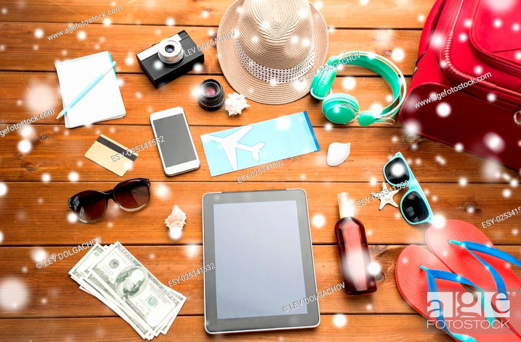 Stock Photo: vacation, winter holidays, tourism and technology concept - tablet pc computer, airplane ticket and travel stuff over snow.