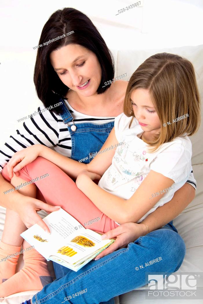 Stock Photo: Little girl sitting on her mother's lap, and reading a book in her bedroom.