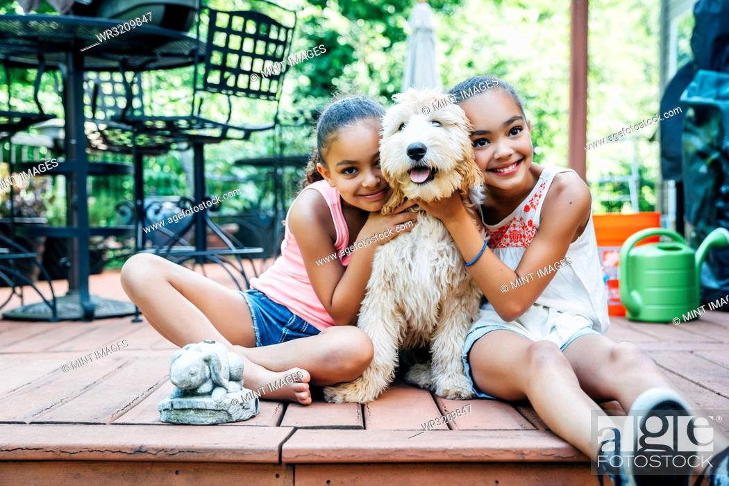 Stock Photo: Mixed Race Sisters Play with Labradoodle Puppy on Porch.