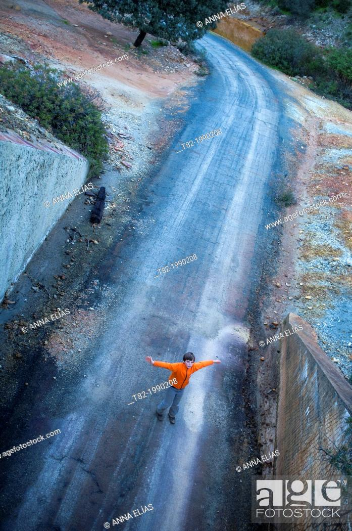 Stock Photo: Runaway overhead view of child with arms outstretched abandoned road playing, Berrocal, Huelva, Andalucia, Spain.