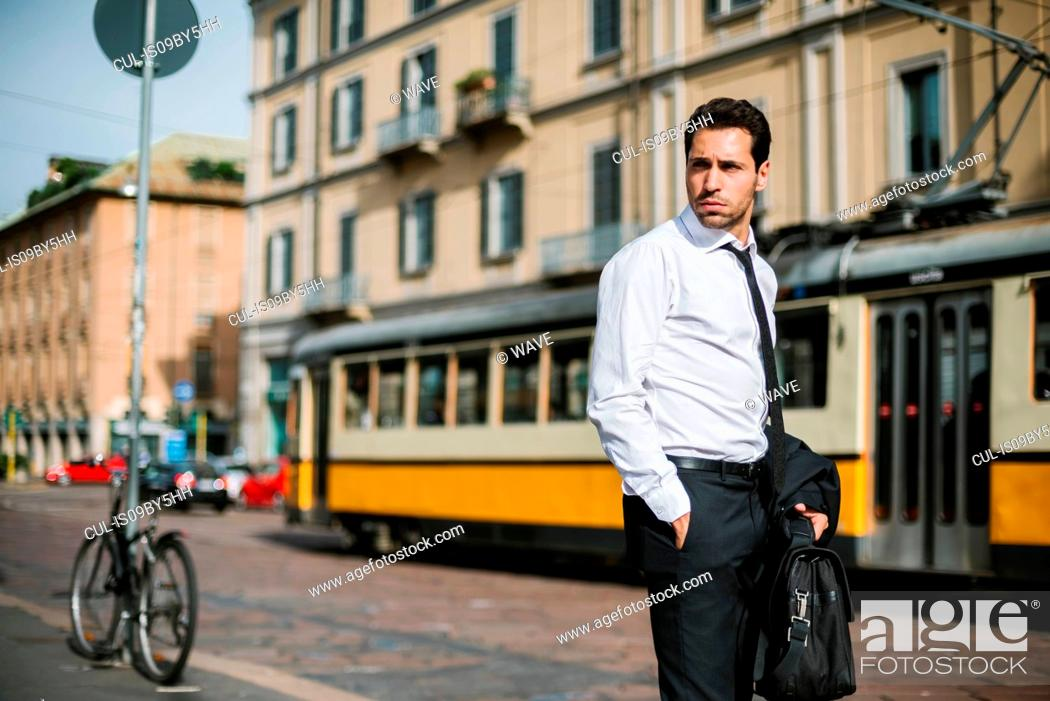 Stock Photo: Mid adult businessman on city street looking over his shoulder.