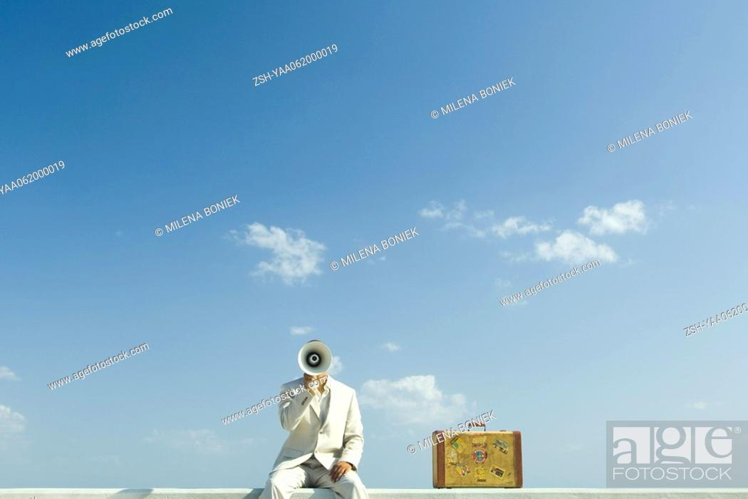Stock Photo: Man sitting on wall beside suitcase, holding megaphone in front of face.