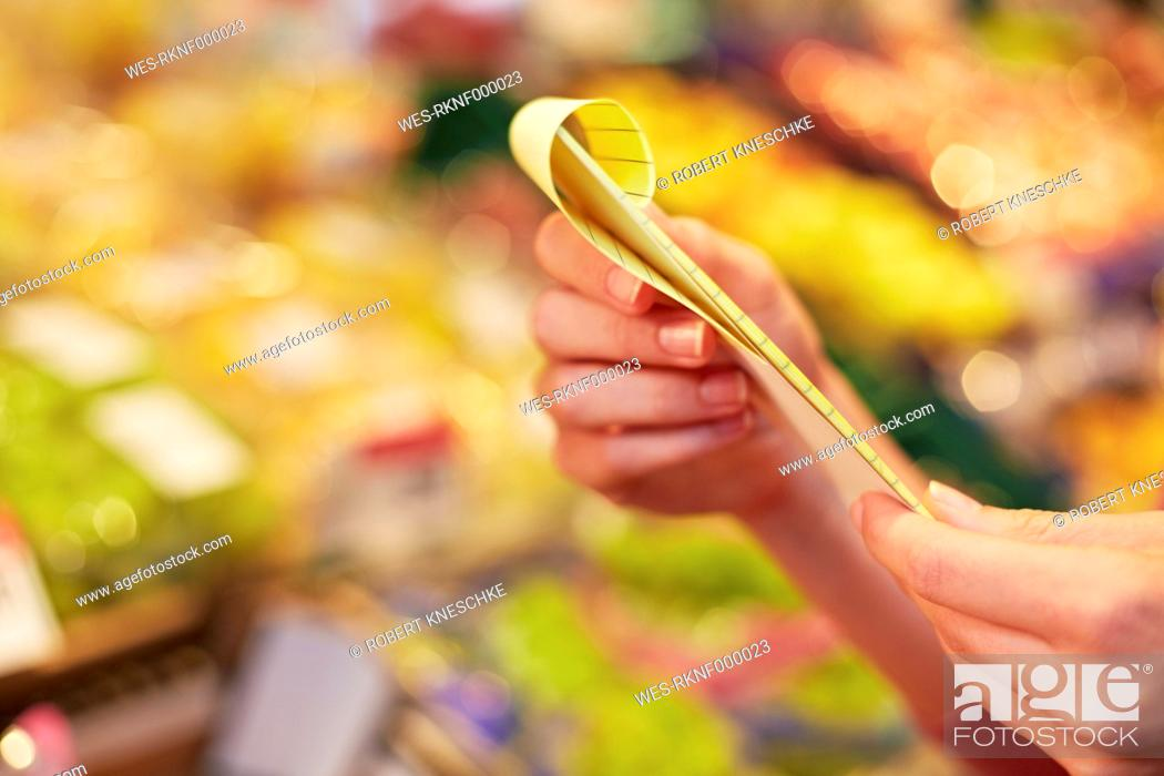 Stock Photo: Germany, Cologne, Human hand holding shopping list in supermarket.