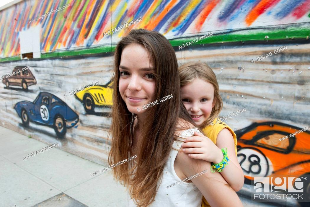 Stock Photo: Teenage girl giving her little sister a piggyback ride, portrait.