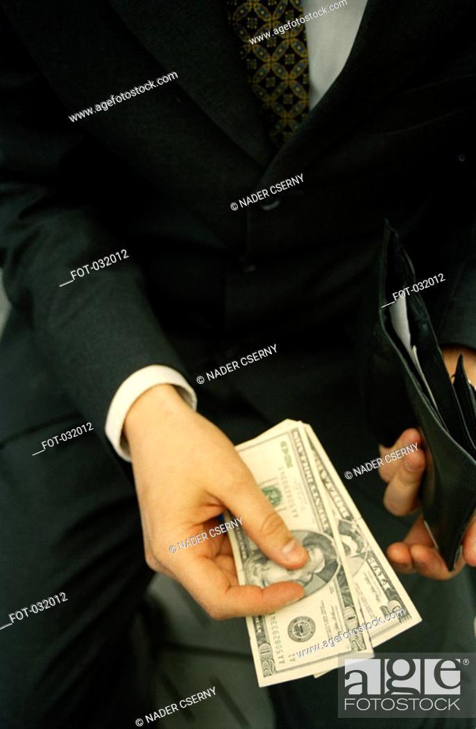 Stock Photo: A businessman paying cash.