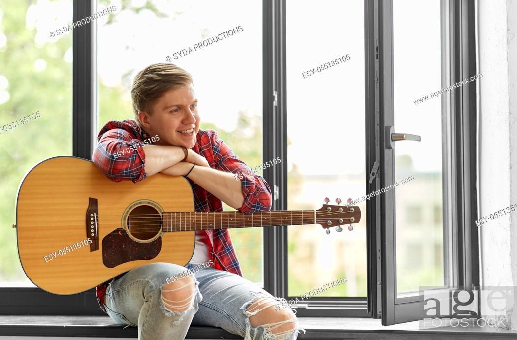 Imagen: young man playing guitar sitting on windowsill.