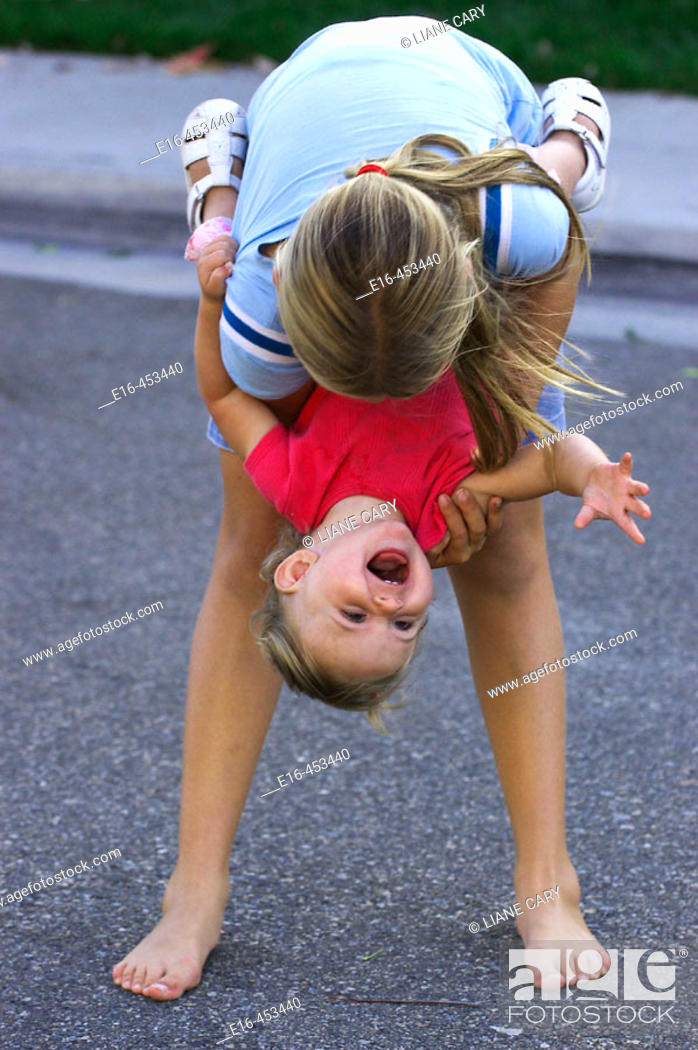 Stock Photo: Girl holding laughing toddler upside down.