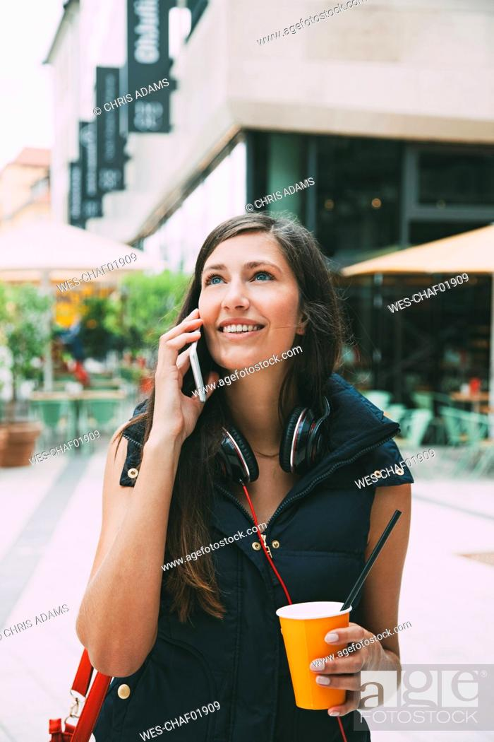 Stock Photo: Portrait of smiling young woman on cell phone with takeaway drink in the city.