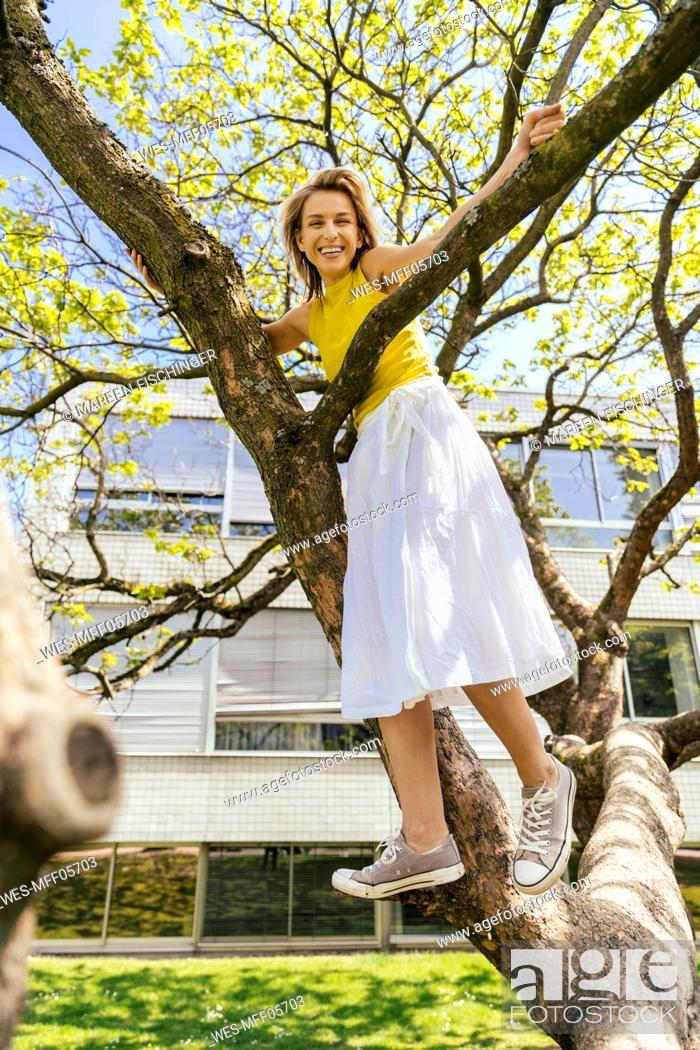 Photo de stock: Portrait of happy woman standing in a tree in a park.