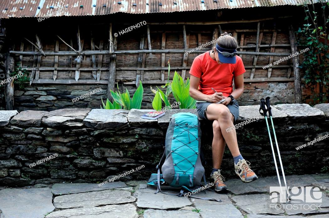 Stock Photo: Woman stops for a break along stone-paved street, Ngadi, Nepal.